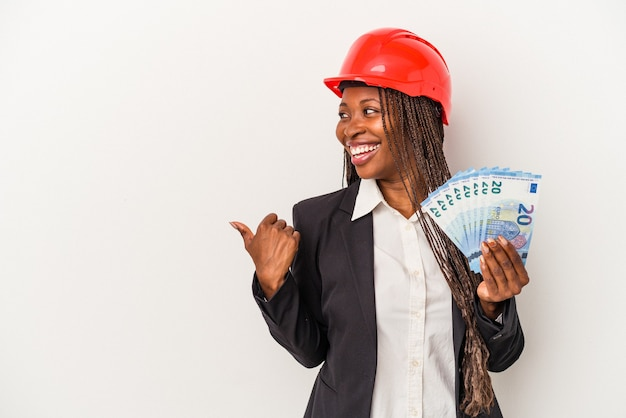 Young african american architect woman holding bills isolated on white background points with thumb finger away, laughing and carefree.