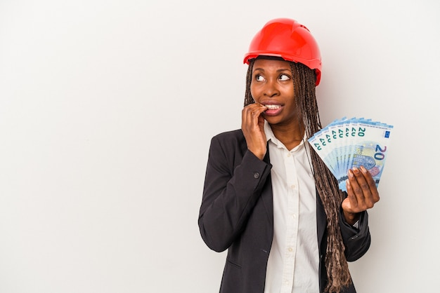 Young african american architect woman holding bills isolated on white background relaxed thinking about something looking at a copy space.