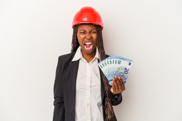 Young african american architect woman holding bills isolated on white background screaming very angry and aggressive.