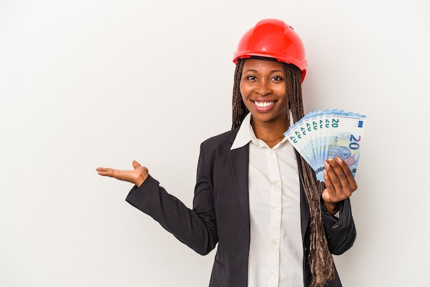 Young african american architect woman holding bills isolated on white background showing a copy space on a palm and holding another hand on waist.