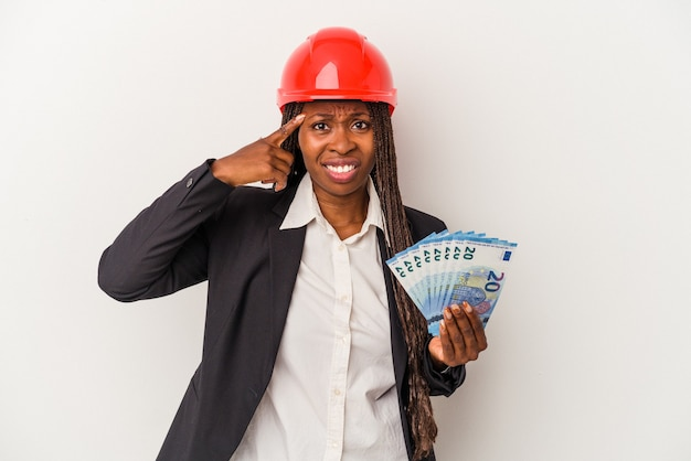 Young african american architect woman holding bills isolated on white background showing a disappointment gesture with forefinger.