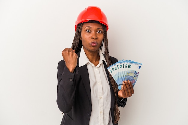 Young african american architect woman holding bills isolated on white background showing fist to camera, aggressive facial expression.