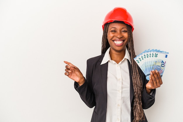 Young african american architect woman holding bills isolated on white background smiling and pointing aside, showing something at blank space.