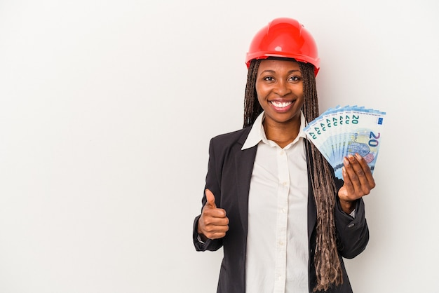 Young african american architect woman holding bills isolated on white background smiling and raising thumb up