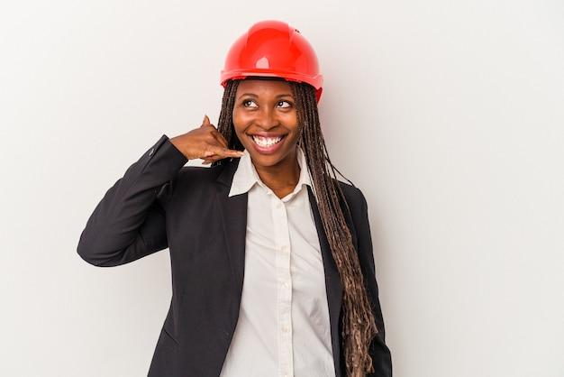 指で携帯電話の呼び出しジェスチャーを示す白い背景で隔離の若いアフリカ系アメリカ人建築家の女性。