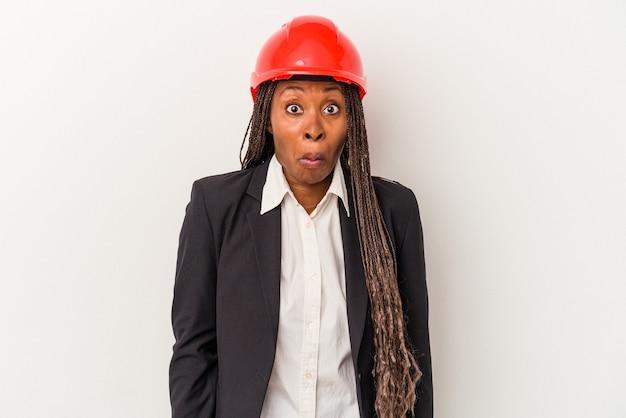 白い背景で隔離の若いアフリカ系アメリカ人建築家の女性は肩をすくめ、目を開けて混乱します。