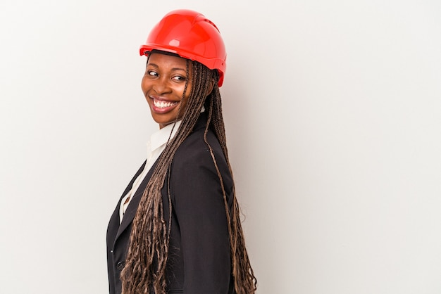 Young african american architect woman isolated on white background looks aside smiling, cheerful and pleasant.