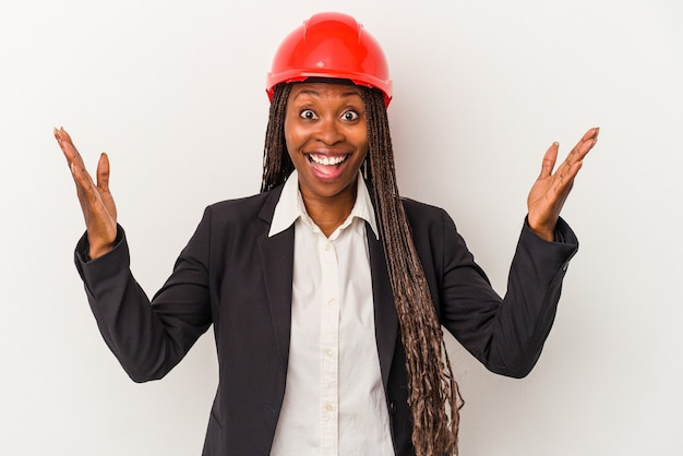 Young african american architect woman isolated on white background receiving a pleasant surprise, excited and raising hands.