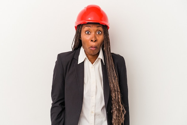 Young african american architect woman isolated on white background shrugs shoulders and open eyes confused.