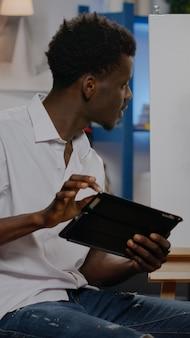 Giovane artista afroamericano che utilizza tablet digitale per progetti di disegno artistico in studio. uomo di colore con un dispositivo di contenimento delle abilità creative per capolavori moderni e belle arti professionali