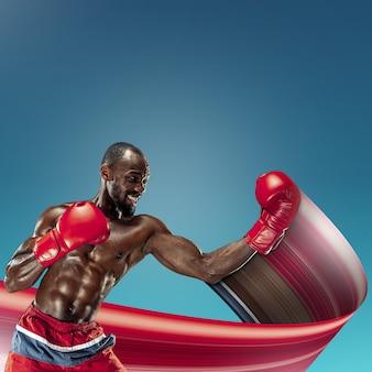 青いスタジオの背景に若いアフリカ系アメリカ人アスリートトレーニング。筋肉の男性モデルボクシング。スポーツ、ボディービル、健康的なライフスタイル、動き、行動の概念。抽象的なデザイン。