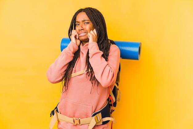 若いアフリカ系アメリカ人のバックパッカーの女性は、手で耳を覆って孤立しました。