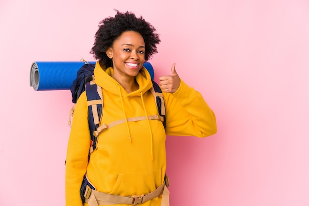 Young african american backpacker woman isolated smiling and raising thumb up