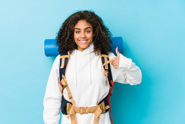 Young african american backpacker woman person pointing by hand to a shirt copy space, proud and confident