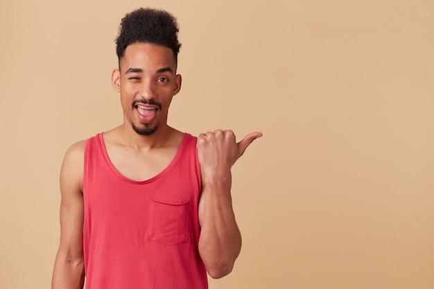 Giovane uomo afroamericano, barbuto con acconciatura afro. indossando canottiera rossa, occhiolino e indicando con il pollice a destra nello spazio della copia, isolato su un muro beige pastello