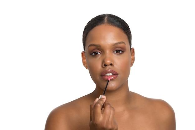 심각 하 게 흰 벽에 립스틱을 적용하는 완벽 하 고 부드러운 피부를 가진 젊은 아프리카 계 미국인 아름다움 모델.