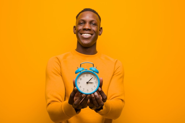 Young african american black man against orange wall holding an alarm clock