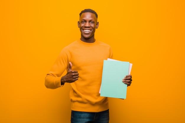 Молодой афроамериканец черный человек против оранжевой стены с книгой