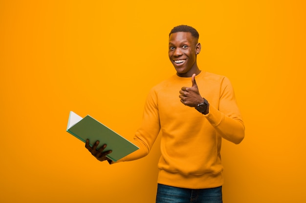 Young african american black man against orange wall with a book