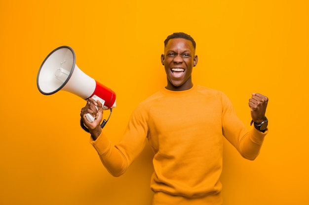 Young african american black man against orange wall with a megaphone