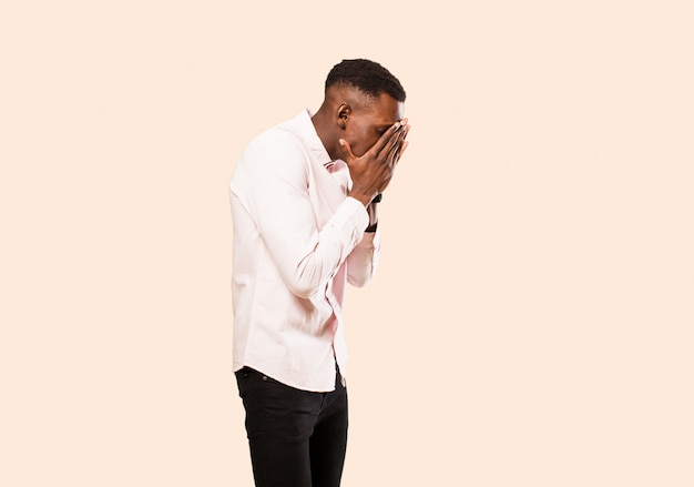 Young african american black man coning eyes with hands with a sad, frustrated look of despair, crying, side view on beige wall