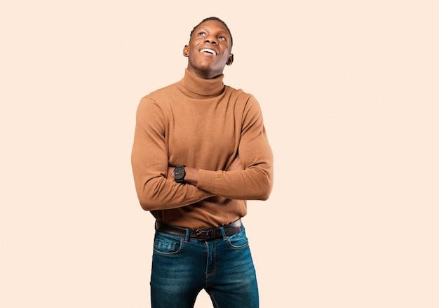 若いアフリカ系アメリカ人の黒人男性の幸せ、誇りと希望に満ちた、疑問や思考を感じて、ベージュの壁に組んだ腕でコピースペースを見上げて
