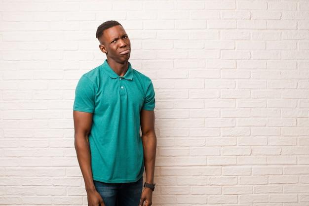 Молодой афроамериканский темнокожий мужчина грустит и плаксивает с несчастным взглядом, плачет с негативным и разочарованным отношением к кирпичной стене