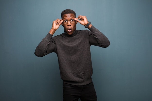 Young african american black man feeling shocked, amazed and surprised, holding glasses with astonished, disbelieving look against grunge wall