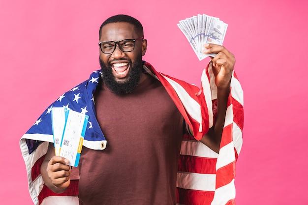 보딩 패스 티켓과 달러 지폐를 들고 있는 젊은 아프리카계 미국인 흑인 남자가 분홍색 배경 위에 격리되어 있습니다.