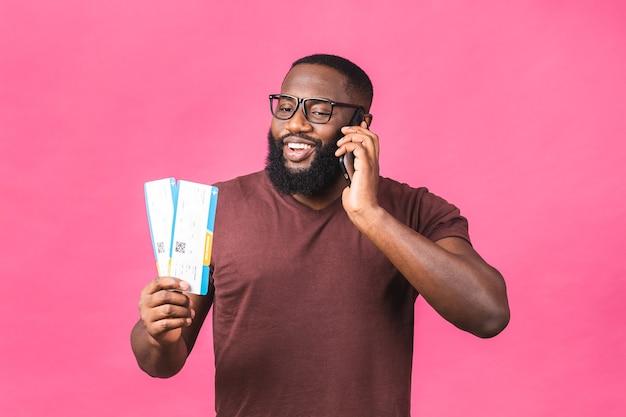 분홍색 배경 위에 절연 보딩 패스 티켓을 들고 젊은 아프리카계 미국인 흑인 남자. 휴대 전화 사용.