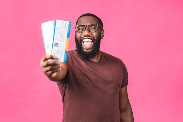 분홍색 배경 위에 절연 보딩 패스 티켓을 들고 젊은 아프리카계 미국인 흑인 남자.