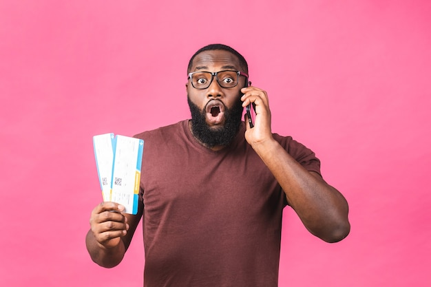Young african american black man holding boarding pass tickets isolated over pink background. using mobile phone.