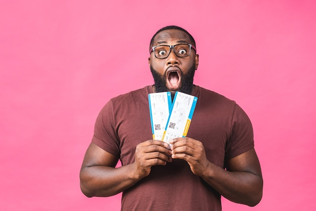 Young african american black man holding boarding pass tickets isolated over pink background.