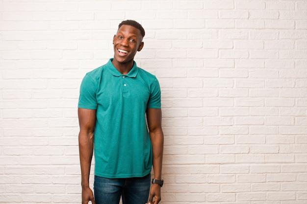 レンガの壁に魅了されショックを受けた表情で興奮し、幸せそうに感じて驚いて、興奮している若いアフリカ系アメリカ人の黒人男性