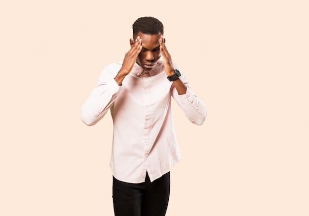 若いアフリカ系アメリカ人の黒人男性がストレスと欲求不満を探して、頭痛で圧力の下で作業し、ベージュの壁の問題に悩んで