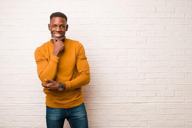 若いアフリカ系アメリカ人の黒人男性のあごに手を幸せで自信を持って式に笑みを浮かべて、疑問に思って、レンガの壁に側を見て