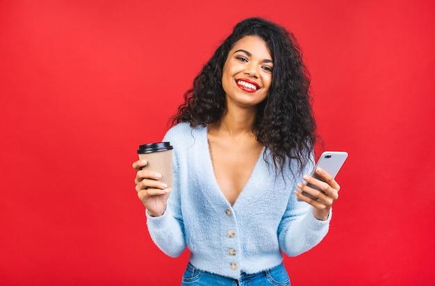 Молодая афро-американская темнокожая женщина, держащая чашку кофе и мобильный телефон, изолирована на красном фоне