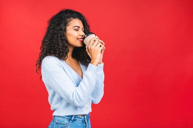 Молодая афро-американская черная женщина держит чашку кофе на красном фоне