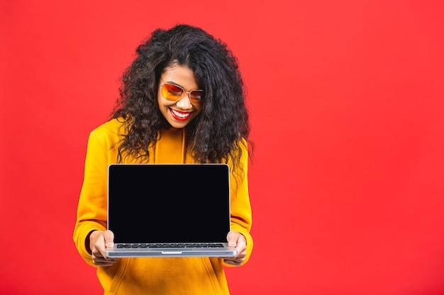 Young african american black woman holding a laptop isolated over red background