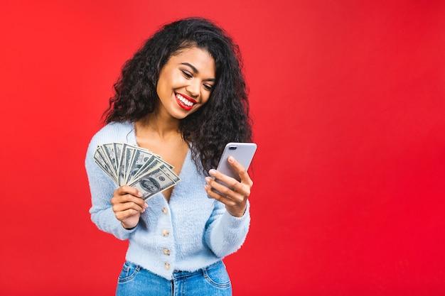 Молодая афро-американская темнокожая женщина держит деньги и мобильный телефон на красном фоне