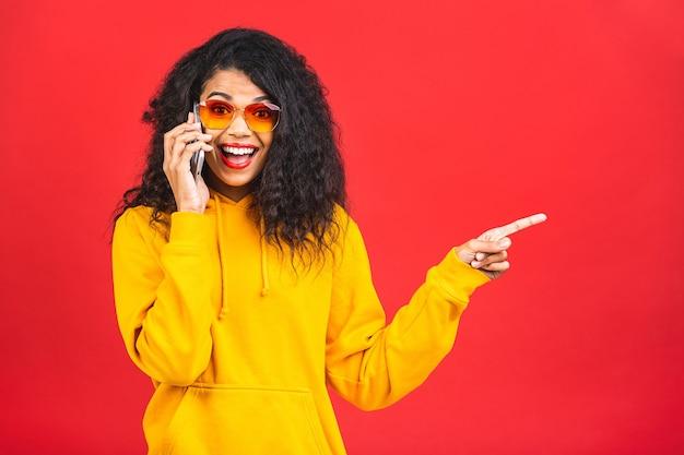 Молодая афро-американская черная женщина разговаривает по мобильному телефону на красном фоне