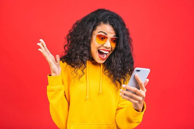 Молодая афро-американская черная женщина с мобильным телефоном на красном фоне