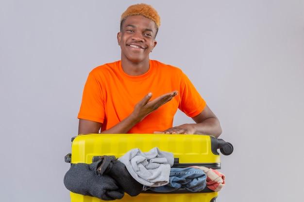 白い背景の上の側に彼の手の腕で指しているカメラの楽観的で陽気な笑顔を見て服の完全な旅行スーツケースとオレンジ色のtシャツを着ている若いアフリカ系アメリカ人の少年