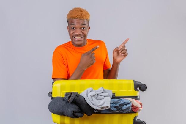 白い背景の上の側に指で指で指しているカメラの楽観的で陽気な笑顔を見て服の完全な旅行スーツケースとオレンジ色のtシャツを着ている若いアフリカ系アメリカ人の少年