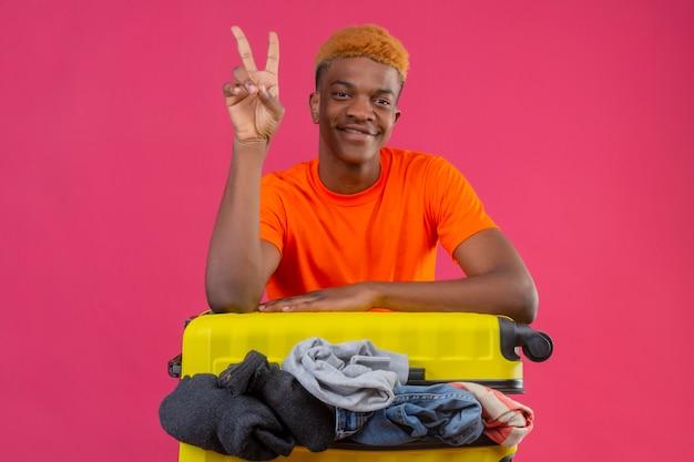 ピンクの背景に2番または勝利のサインを示すカメラの楽観的で陽気な笑顔を見て服の完全な旅行スーツケースとオレンジ色のtシャツを着ている若いアフリカ系アメリカ人の少年
