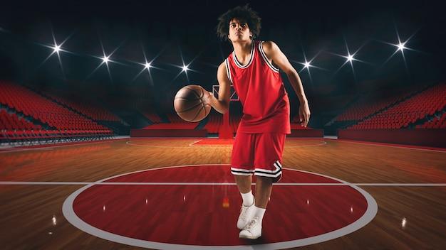 スタジアムの真ん中にバスケットボールを持つ若いアフリカ系アメリカ人の少年