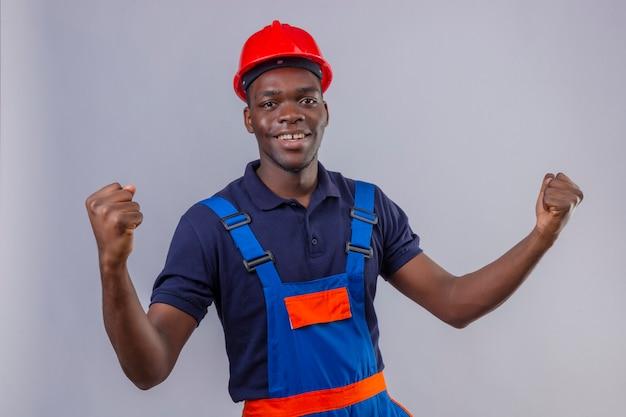 Молодой афро-американский строитель в строительной форме и защитном шлеме, сжимая кулаки, улыбается, стоя со счастливым лицом, празднует победу