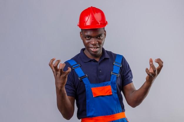 Молодой афро-американский строитель в строительной форме и защитном шлеме сумасшедший и сумасшедший, с агрессивным выражением лица и поднятыми руками