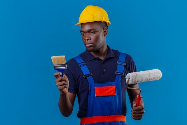 Молодой афро-американский строитель в строительной форме и защитном шлеме, держащий кисть и малярный валик, смотрит на кисть с серьезным выражением лица, стоя на синем