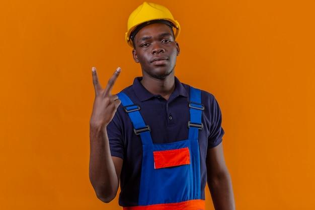 Молодой афро-американский строитель в строительной форме и защитном шлеме выглядит уверенно, показывая победу поет, стоя на оранжевом